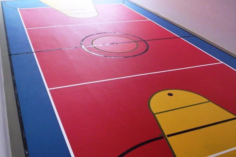 Foto - Quadra Poliesportiva - vermelho área de vôlei, azul nos recuos e amarelo nos garrafões de basquete.